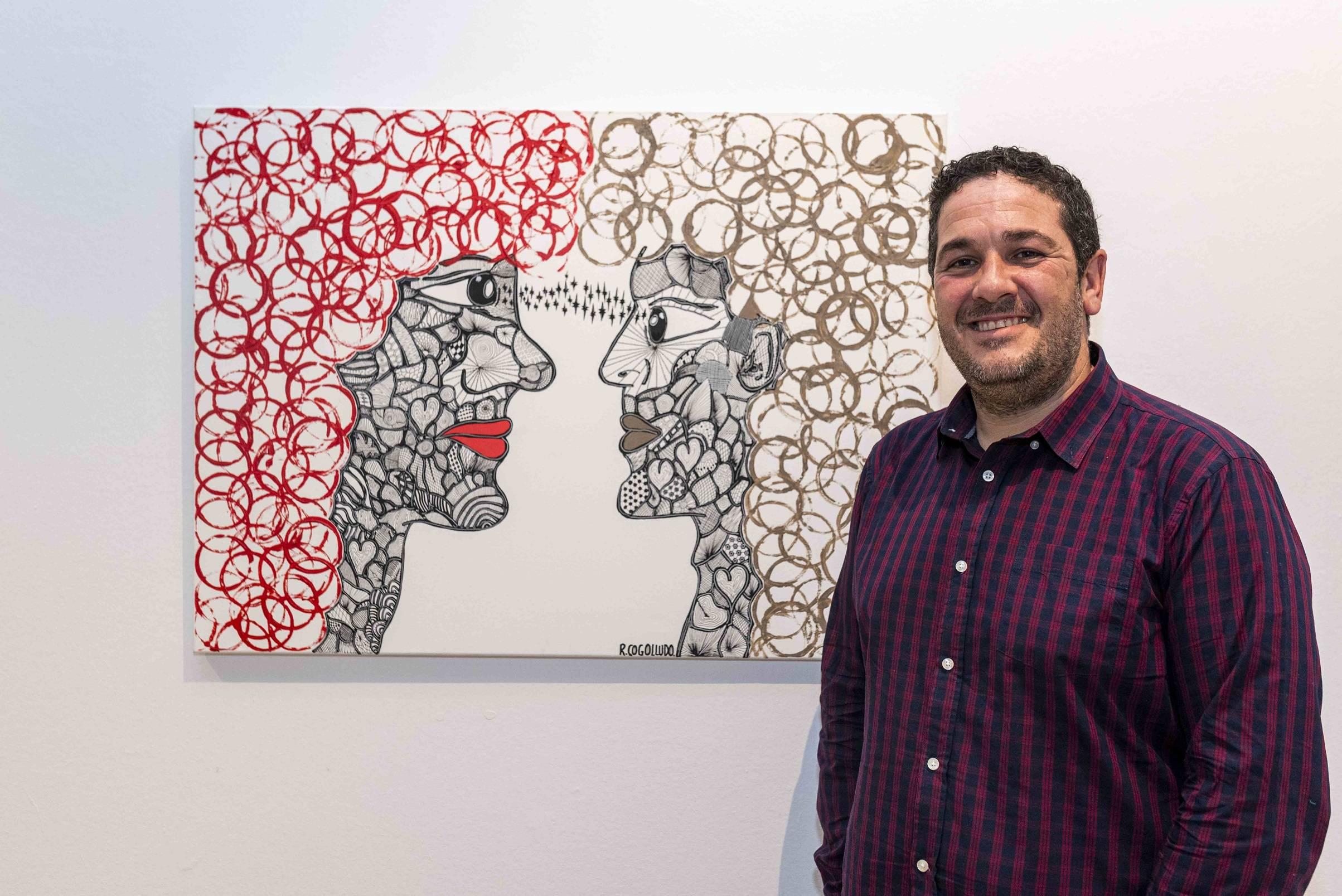 El artista con algunos de los cuadros de la exposición.