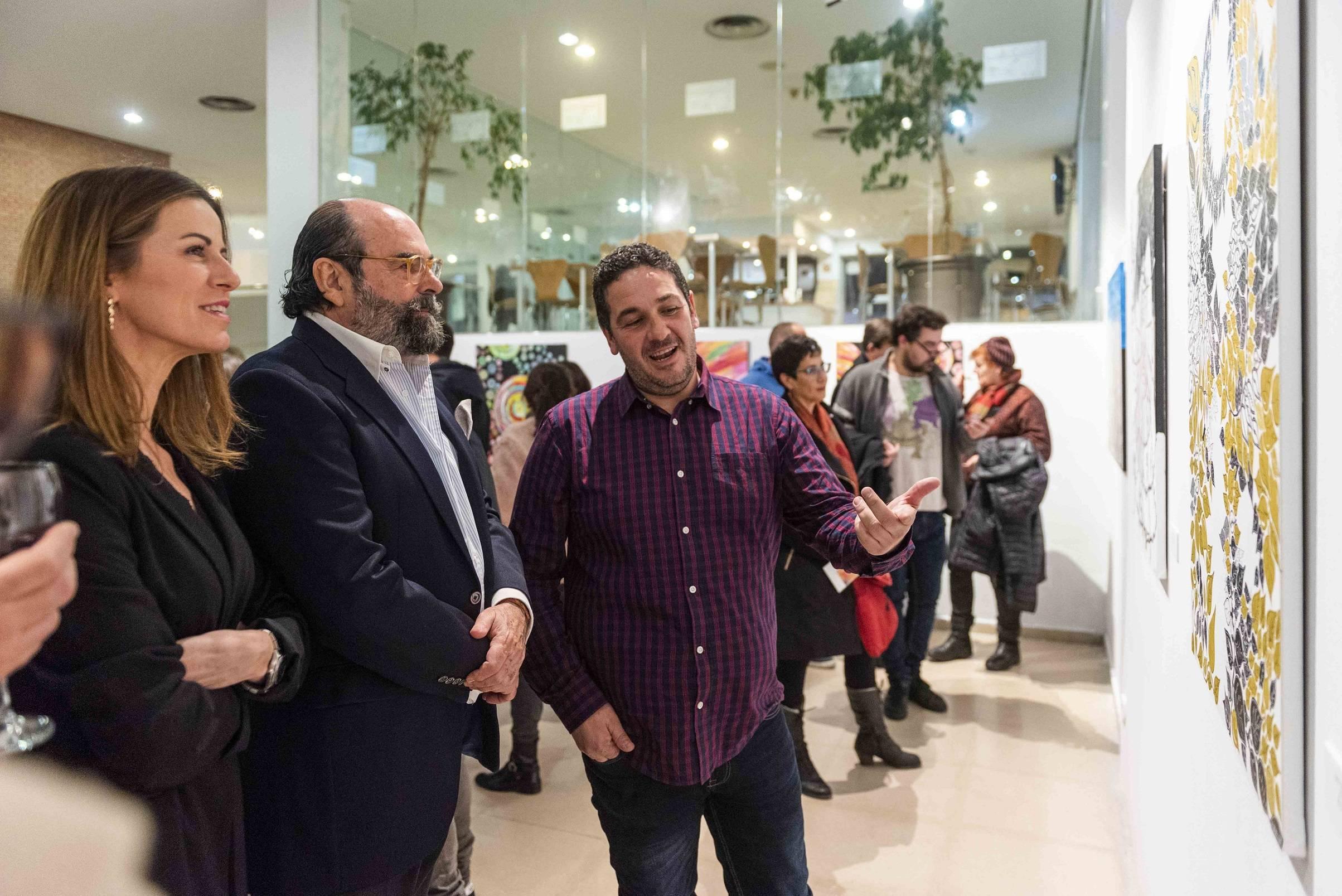 Raúl Cogolludo mostrándole al concejal de Cultura algunas de sus obras.