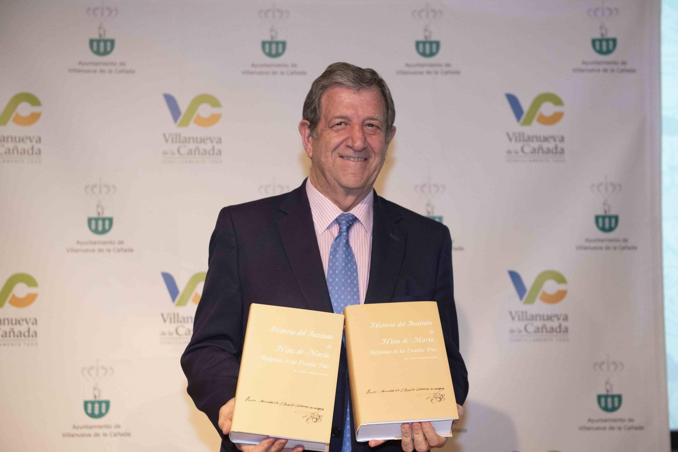 El alcalde posando con dos publicaciones que las Escolapias le entregaron durante el acto.