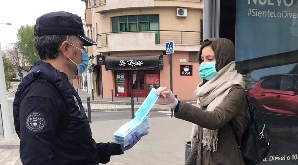 Un policía local hace entrega de una mascarilla a una usuaria del transporte público.