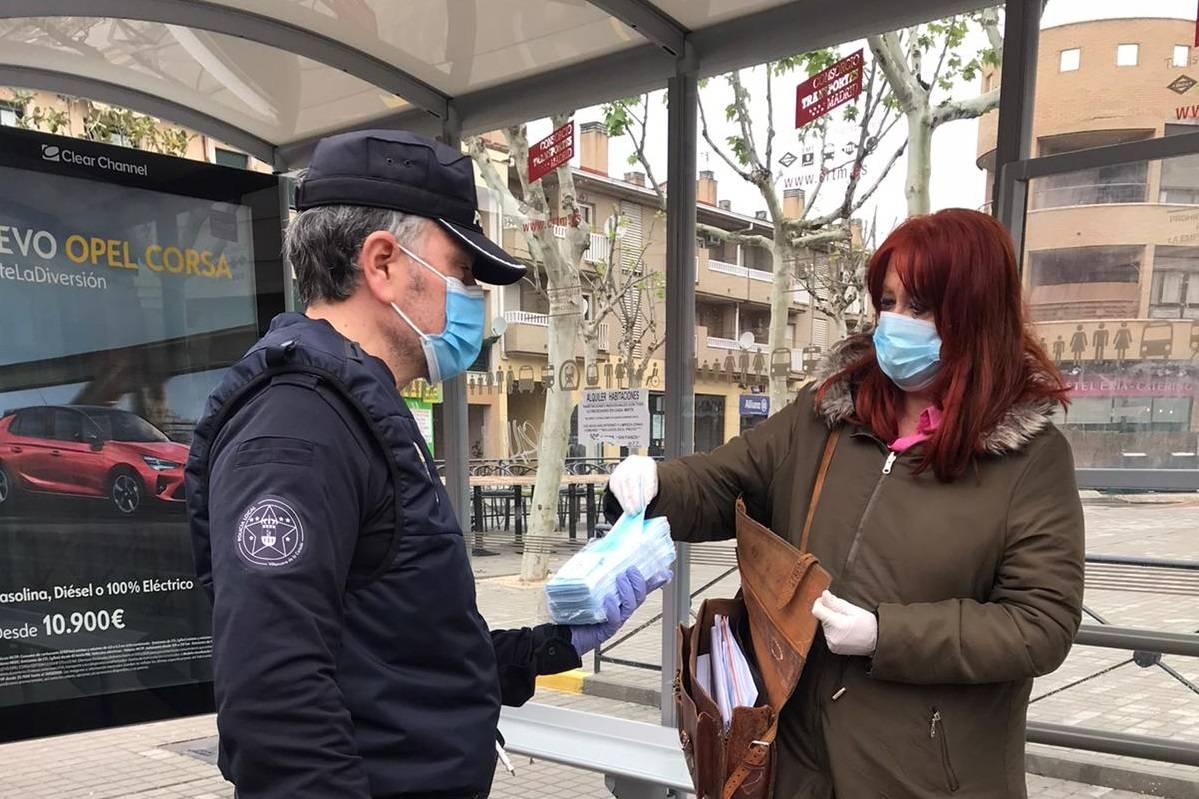 Un miembro de la policía local entregando una mascarilla a una vecina.