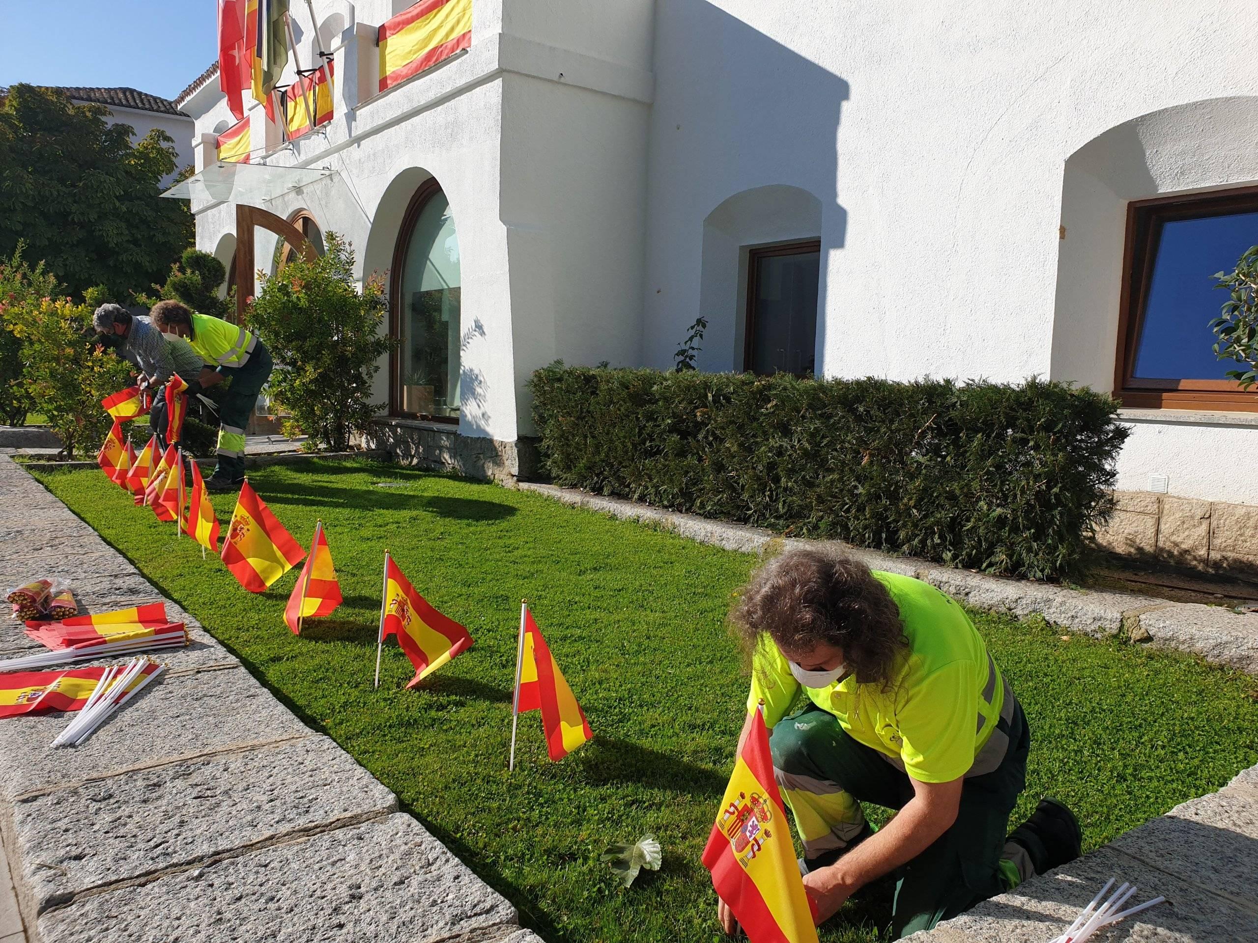 Operarios colocando las banderas.