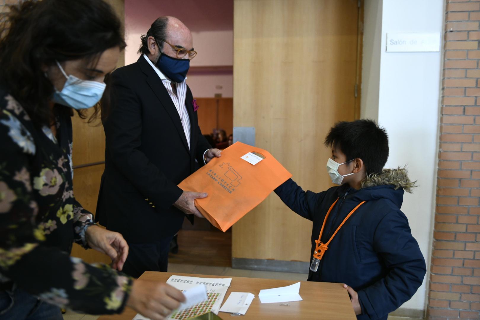 El concejal de cultura entregando el regalo a uno de los participantes.