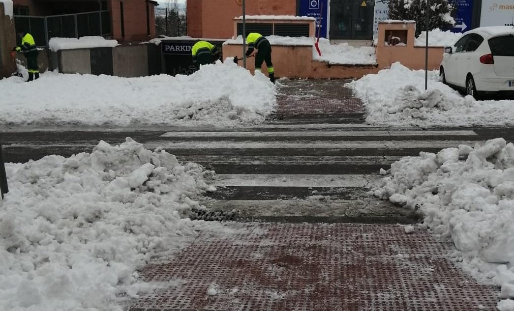Operarios municipales retirando nieve de pasos de peatones.