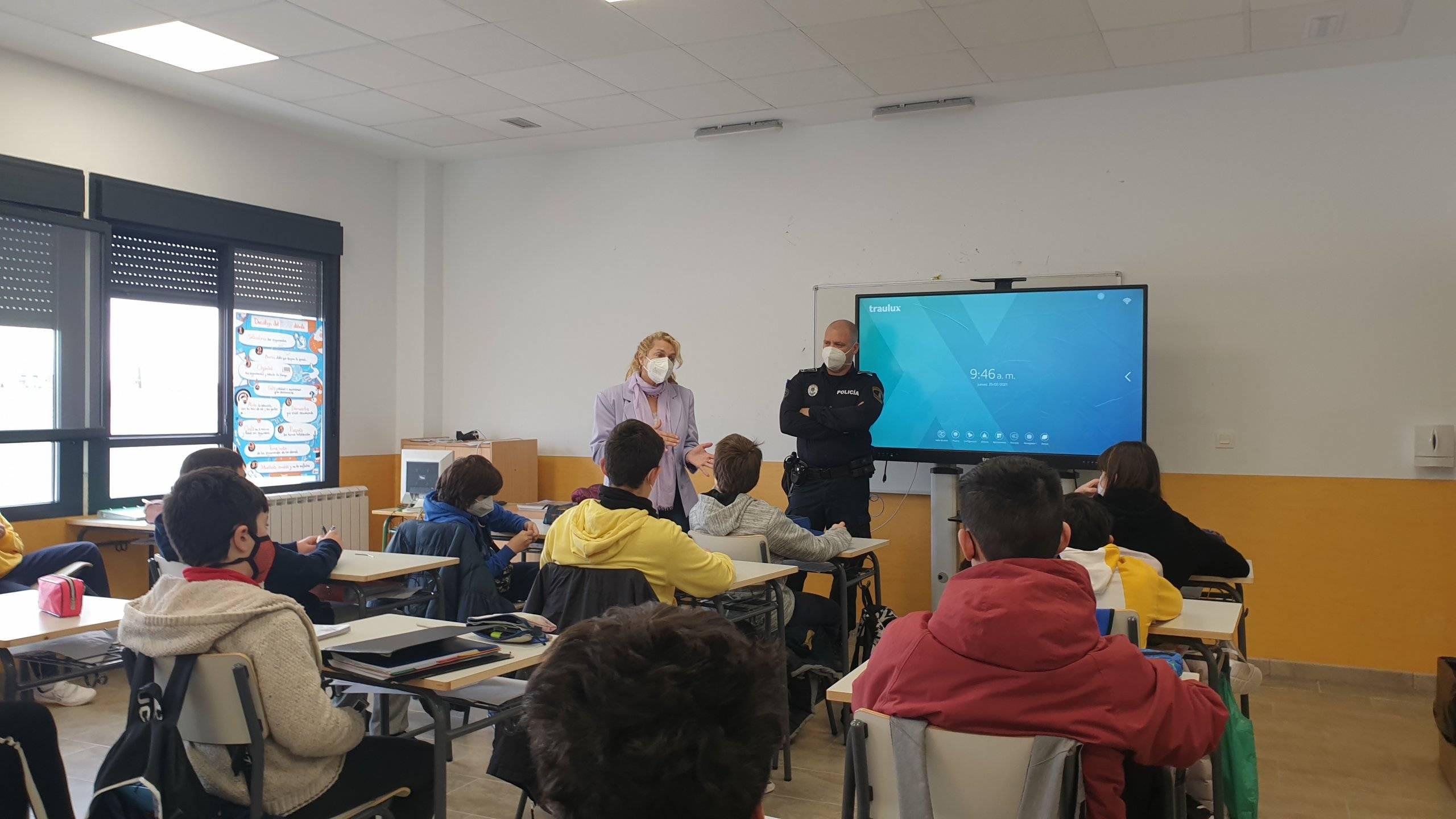 La directora del CEIPSO Padre Garralda junto al policía de la Unidad de Agente Tutor en un aula con alumnos.