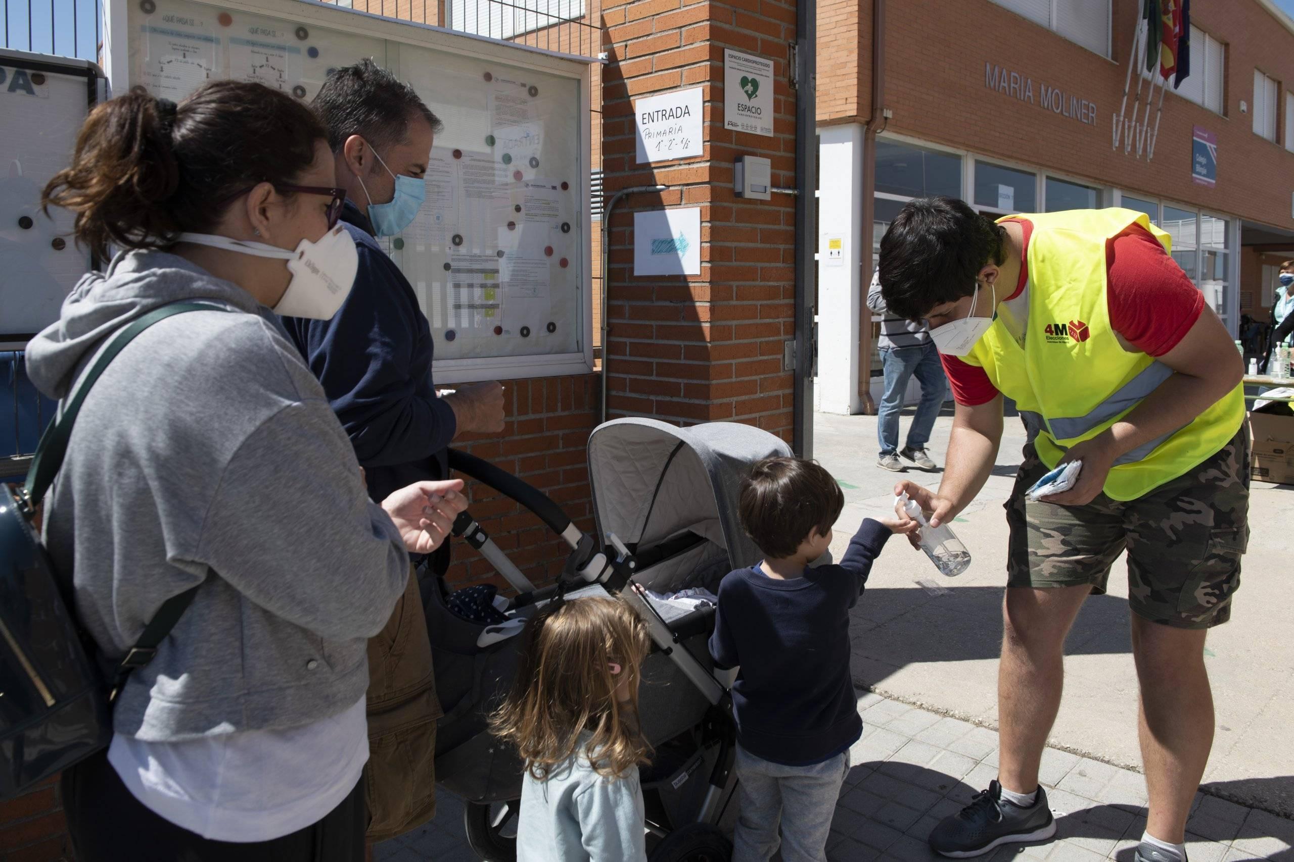 Dos niños desinfectándose las manos a la entrada a un colegio electoral.