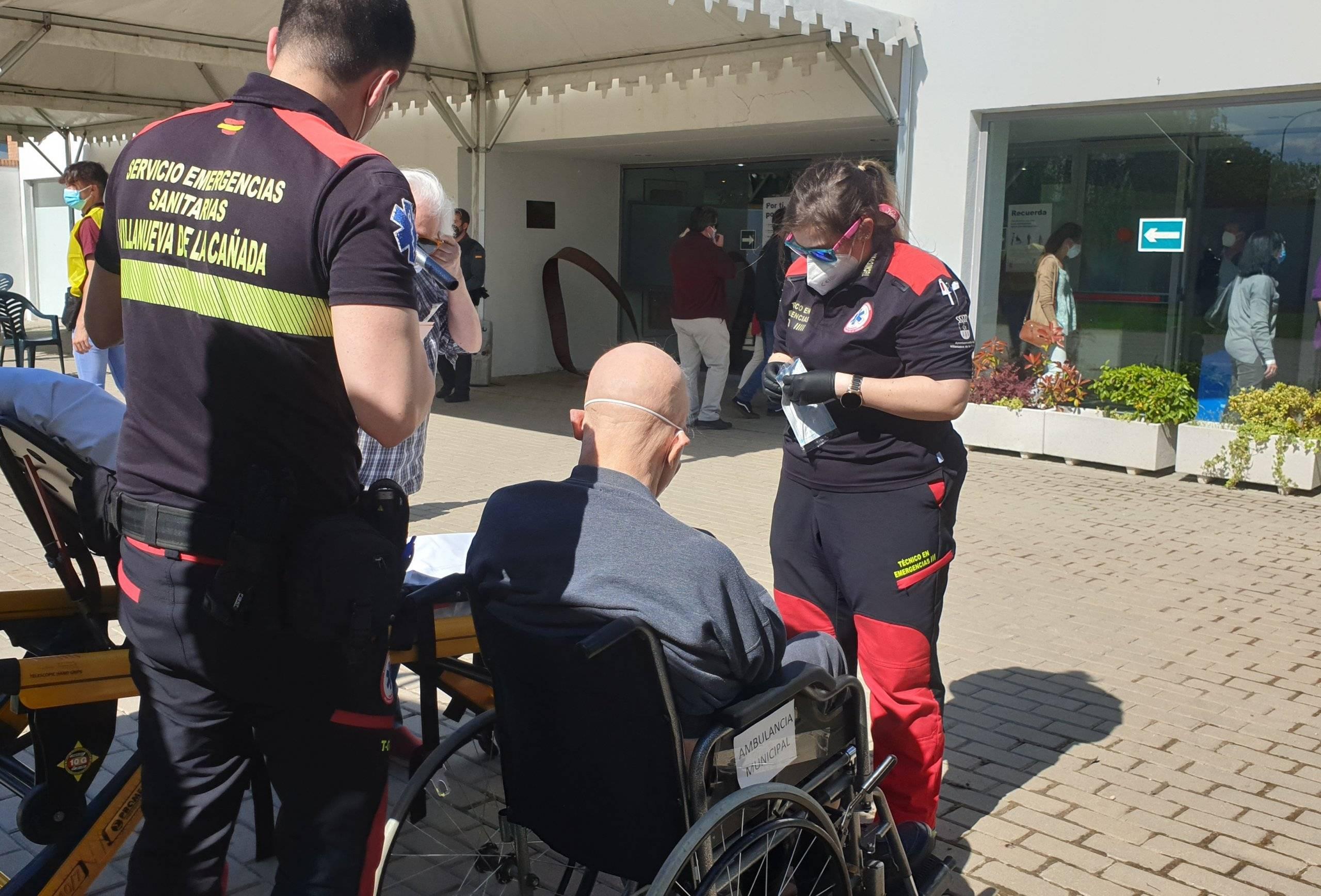 Técnicos del Servicio Municipal de Emergencias Sanitarias trasladan en silla de ruedas a una persona con movilidad reducida al colegio electoral.