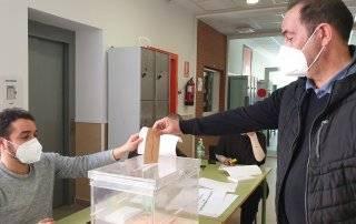 Un vecino introduciendo su voto en la urna.