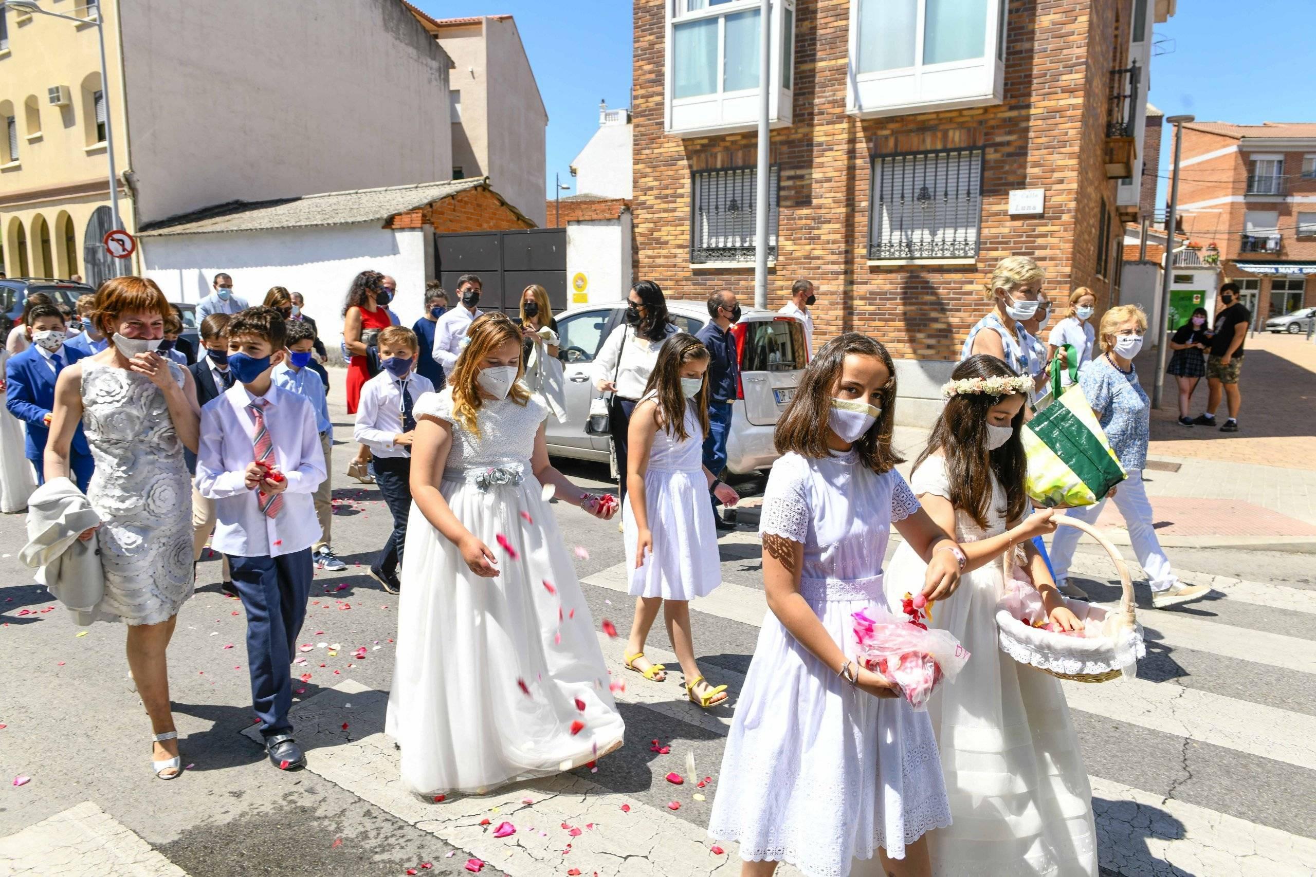 Niños vestidos de comunión alfombrando las calles con pétalos de rosas.