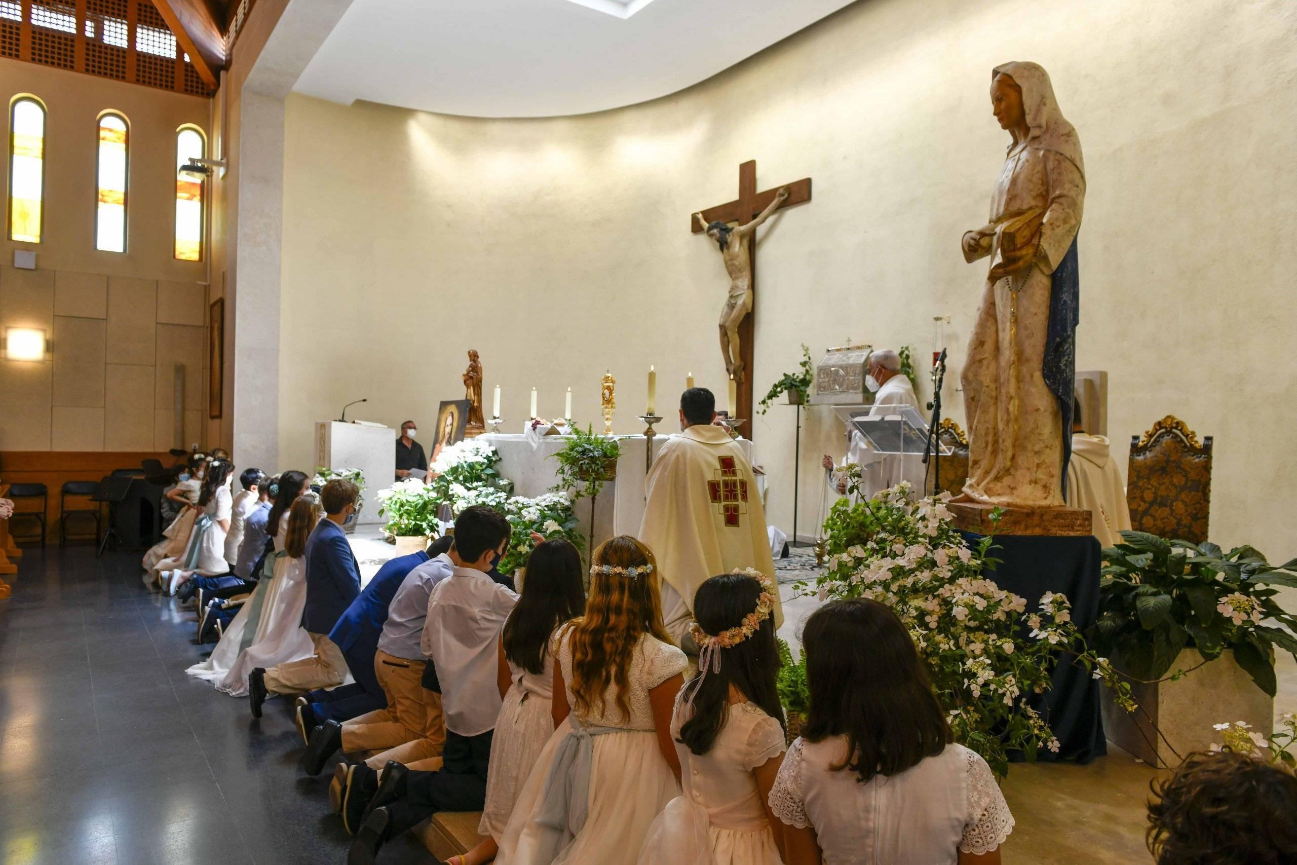 Niños, junto a los párrocos del municipio, en el altar de la parroquia San Carlos Borromeo.
