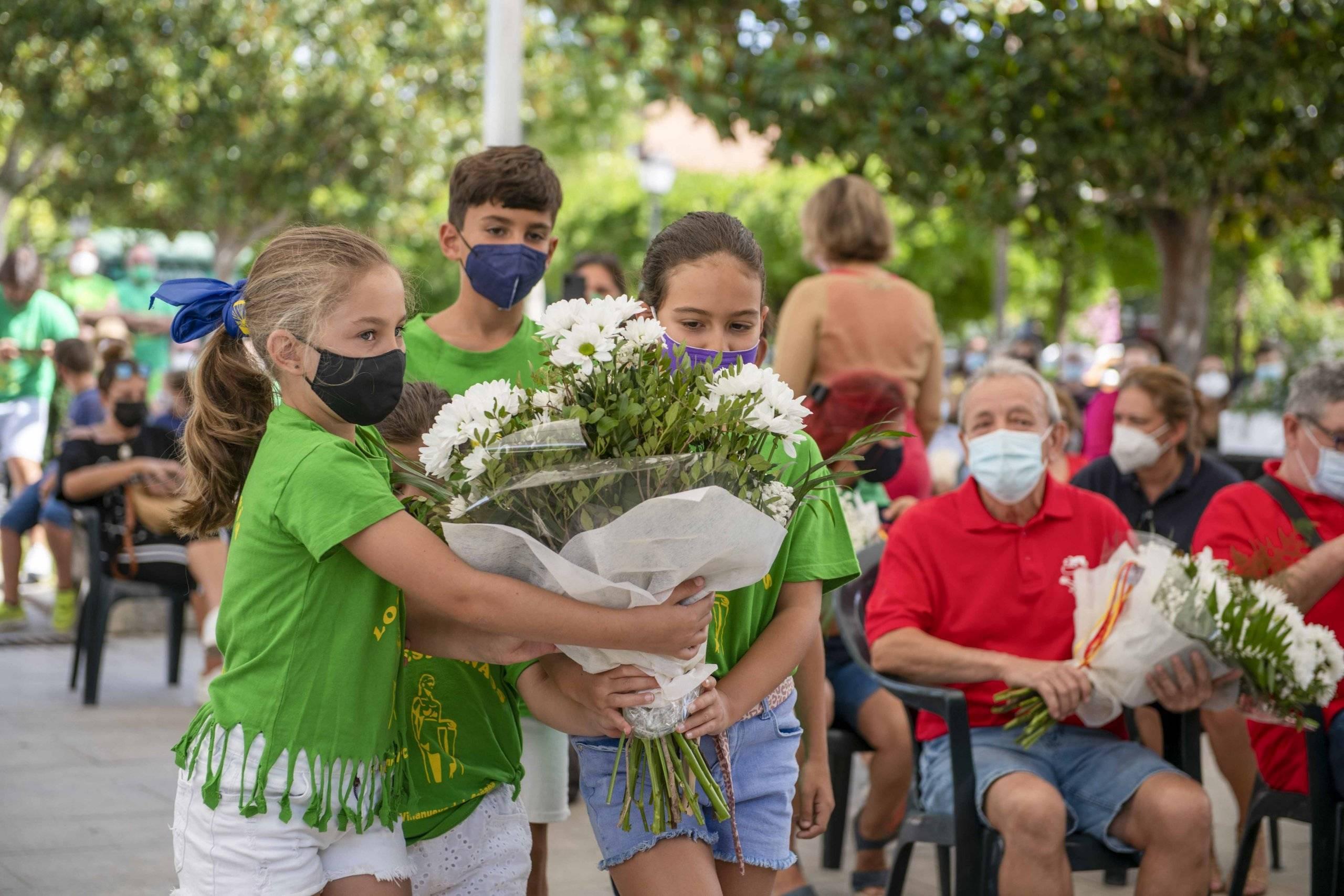 Varios niños de la peña Los Despernaos portando un ramo de camino al altar.