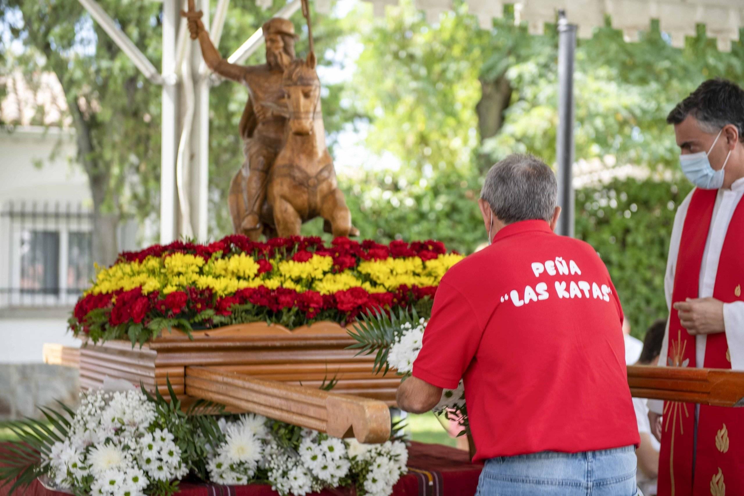 Un representante de la peña Las Katas depositando ante la talla del santo un ramo de flores.