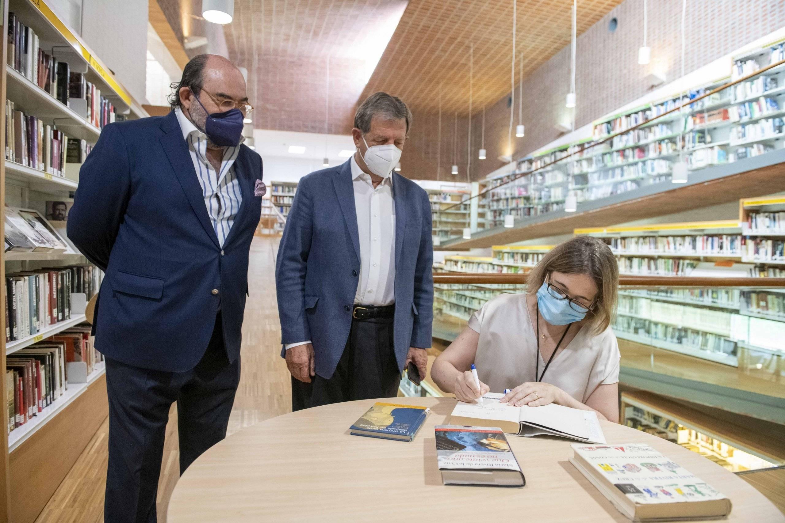 La consejera de Cultura, Turismo y Deporte firmando uno de sus libros, ubicado en la Biblioteca, ante el alcalde y el concejal de Cultura.