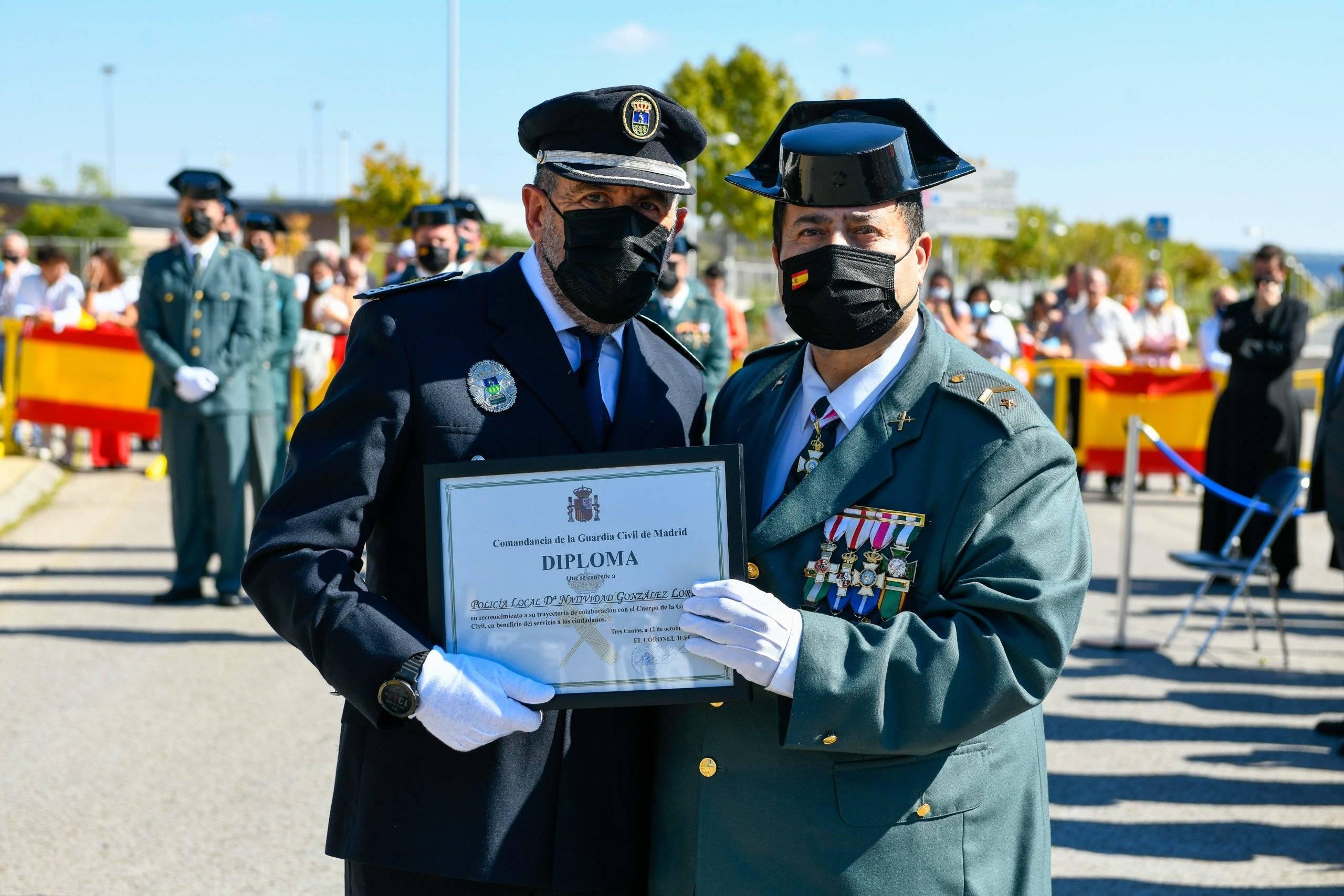 El inspector de Policía Local recoge de manos del subteniente jefe de la Guardia Civil el diploma concedido a una agente de Policía Local.