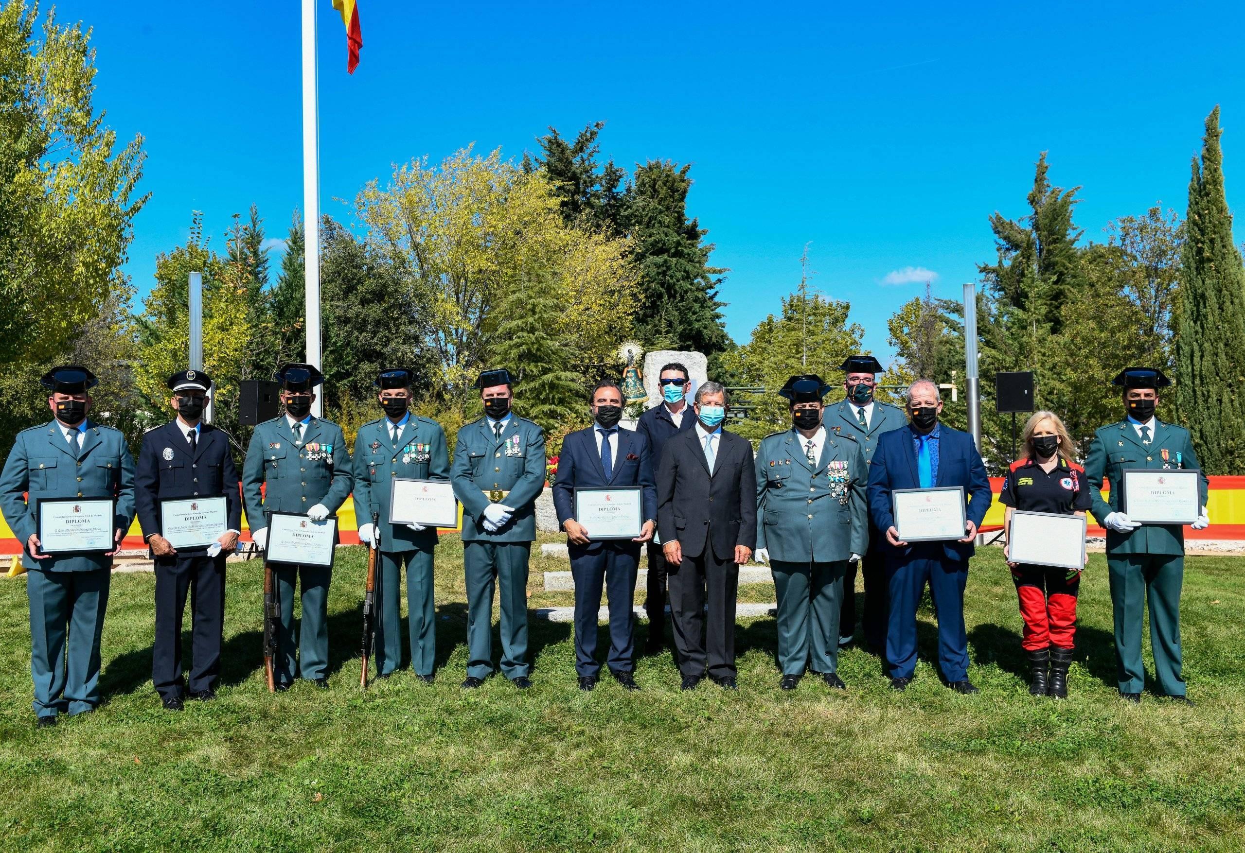 El alcalde y el subteniente jefe del cuartel de la Guardia Civil junto a los galardonados en el acto.