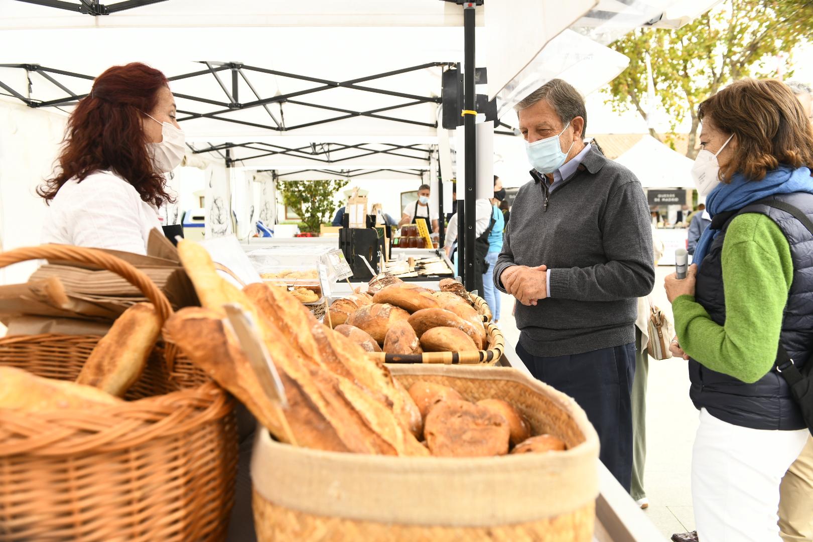 El alcalde y la coordinadora de la CM visitando el puesto de pan ecológico.